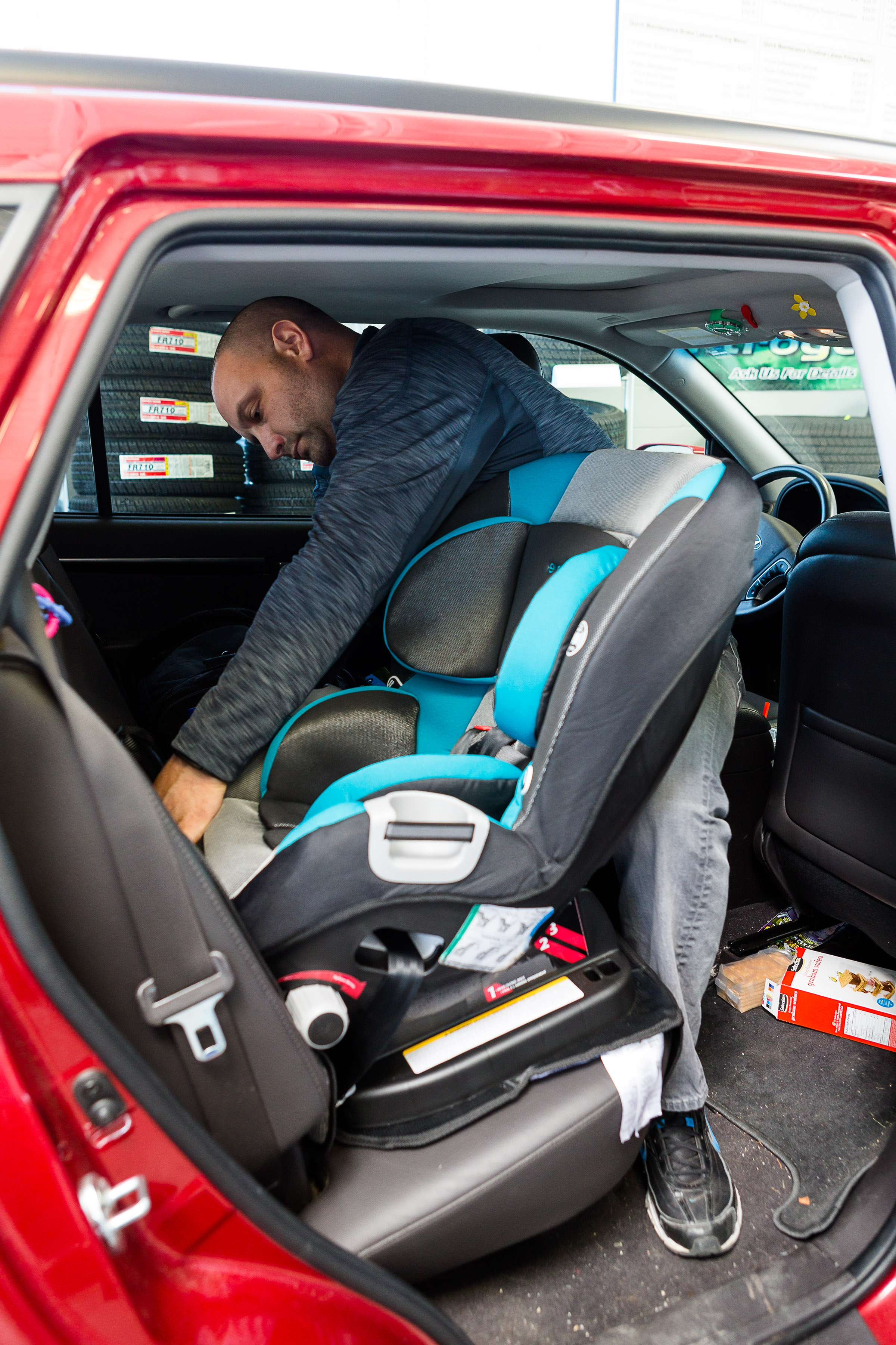A Certified Car Seat Technician Demonstrates To Parent The Pinch Test By Grabbing Loose Shoulder Strap Of Childs Check How Tight